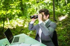 Jeune homme bel d'affaires de sourire au bureau de table de travail avec l'ordinateur portable dans la forêt verte avec les concu Photos stock