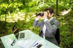Jeune homme bel d'affaires de sourire au bureau de table de travail avec l'ordinateur portable dans la forêt verte avec les concu Image stock