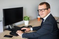 Jeune homme bel d'affaires utilisant l'ordinateur dans le bureau moderne photos stock