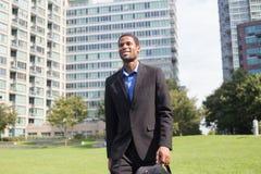 Jeune homme bel d'Afro-américain marchant pour travailler, regardant l'escroquerie Images libres de droits