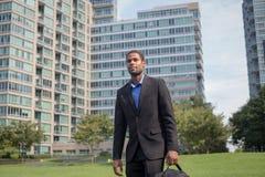 Jeune homme bel d'Afro-américain marchant pour travailler, regardant le sha Photos libres de droits