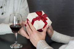 Jeune homme bel dans la chemise blanche donnant le présent à son amie tandis que dînez romantique photo libre de droits