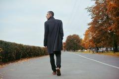 Jeune homme bel dans le manteau Homme bien habillé à la mode posant dans le manteau élégant Garçon sûr et focalisé extérieur à l' image libre de droits