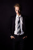 Jeune homme bel dans un costume et une chemise blanche et lien dans le style formel dans le studio sur un fond noir Photographie stock libre de droits