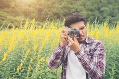Jeune homme bel de hippie photographiant avec le rétro appareil-photo avec image stock