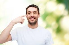 Jeune homme bel de sourire indiquant des yeux photographie stock libre de droits