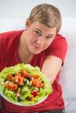 Jeune homme bel disposant à manger de la salade saine fraîche photographie stock