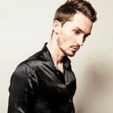 Jeune homme bel élégant dans la chemise en soie noire Portrait de mode de studio Images stock