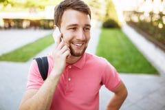Jeune homme bel marchant autour de la ville et parlant au téléphone, hippie photographie stock