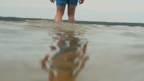 Jeune homme bel musculaire marchant dans l'eau au lac clips vidéos