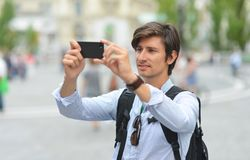 Jeune homme bel photographiant avec le téléphone intelligent mobile Photographie stock libre de droits