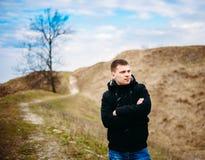 Jeune homme bel resté dans le domaine, pré en Autumn Day Photo stock