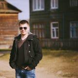 Jeune homme bel restant près de la vieille maison en bois en automne ou PS Photos libres de droits