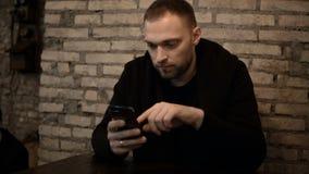 Jeune homme bel s'asseyant dans le café avec le mur de briques et à l'aide du smartphone, passant en revue seul l'Internet Photos stock