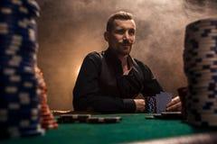 Jeune homme bel s'asseyant derrière la table de tisonnier avec des cartes et des puces Photographie stock libre de droits