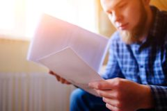 Jeune homme bel s'asseyant sur le divan et les montres une feuille de travail photos stock