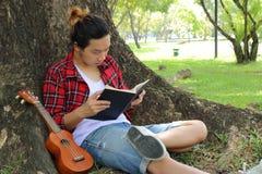 Jeune homme bel s'asseyant sur une herbe verte et lisant un livre en parc Photos stock