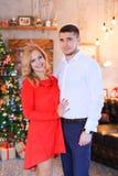 Jeune homme bel se tenant avec la femme portant la robe rouge près de l'arbre de Cristmas Photos libres de droits