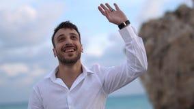 Jeune homme bel souriant heureusement avec une expression stup?faite ? d'autres et ? la main de ondulation cyprus Paphos clips vidéos