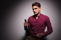 Jeune homme bel tenant une bouteille de vin Images libres de droits