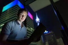 Jeune homme bel utilisant l'ordinateur portable contre le vitrail avec la vue o image stock