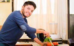 Jeune homme bel utilisant le chandail bleu coupant des légumes sur la table de cuisine, souriant heureusement Image stock