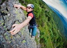 Jeune homme blanc escaladant un mur escarpé Photos stock