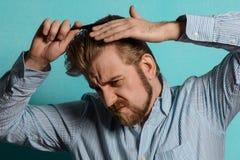 Jeune homme blond dans le peigne de chemise rayée ses cheveux Photographie stock