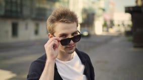 Jeune homme blond enlevant des lunettes de soleil et le clignotement banque de vidéos