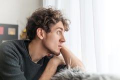 Jeune homme bouclé beau observant par l'attente de douleur de peine de tristesse de concept de fenêtre images libres de droits