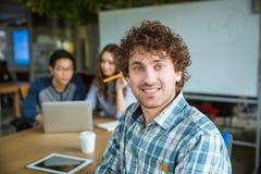 Jeune homme bouclé positif bel étudiant ainsi que des amis Image stock