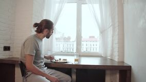 Jeune homme buvant la maison de Juice And Having Breakfast At clips vidéos