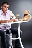 Jeune homme buvant martini avec l'ours de nounours Photos stock