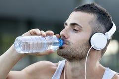 Jeune homme buvant une certaine eau d'une bouteille après la formation images stock