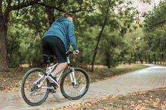 Jeune homme caucasien allant à vélo en parc photographie stock