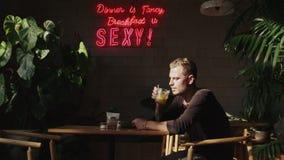 Jeune homme caucasien attendant sa date se reposant en café banque de vidéos