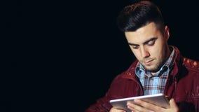 Jeune homme caucasien avec la tablette dans la ville la nuit banque de vidéos