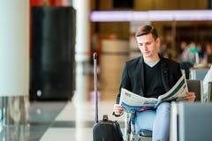 Jeune homme caucasien avec le journal à l'aéroport tout en attendant l'embarquement Costume de port de jeune homme d'affaires occ Photographie stock libre de droits