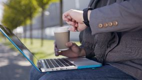 Jeune homme caucasien beau habillé dans la veste et l'écharpe, se reposant sur le banc avec l'ordinateur portable et un texte de  banque de vidéos