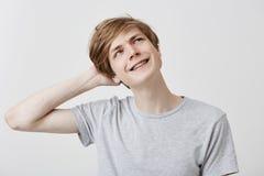Jeune homme caucasien perplexe naïf dans le T-shirt gris avec les cheveux justes et les yeux bleus regardant vers le haut avec co Photo libre de droits