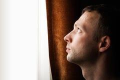 Jeune homme caucasien regardant dans la fenêtre lumineuse Images libres de droits