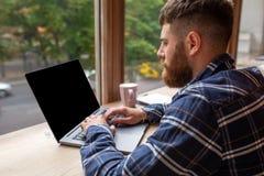 Jeune homme causant par l'intermédiaire du filet-livre pendant la pause dans le café, mâle s'asseyant dans l'ordinateur portable  image libre de droits