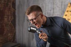 Jeune homme chantant avec le microphone Photos stock
