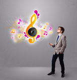 Jeune homme chantant et écoutant la musique avec les notes musicales Photographie stock libre de droits