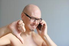 Jeune homme chauve bel en verres noirs parlant au téléphone Verticale de plan rapproché d'un homme Mauvaise nouvelle, tristesse U photos libres de droits