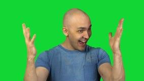 Jeune homme chauve heureux sur le fond vert banque de vidéos