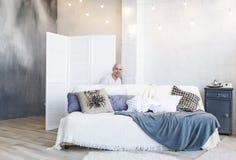 Jeune homme chauve se cachant derrière un sofa à la maison Cache-cache Images stock