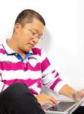 Jeune homme chinois s'asseyant avec un ordinateur portatif photographie stock