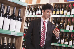 Jeune homme choisissant le vin dans un magasin de vins et de spiritueux image libre de droits