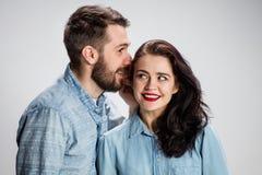 Jeune homme chuchotant à la femme un secret Photographie stock libre de droits